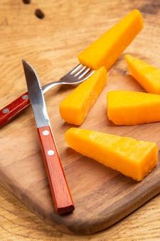 Vista dal basso formaggio su forchetta fette di coltello da formaggio su tagliere su superficie di legno