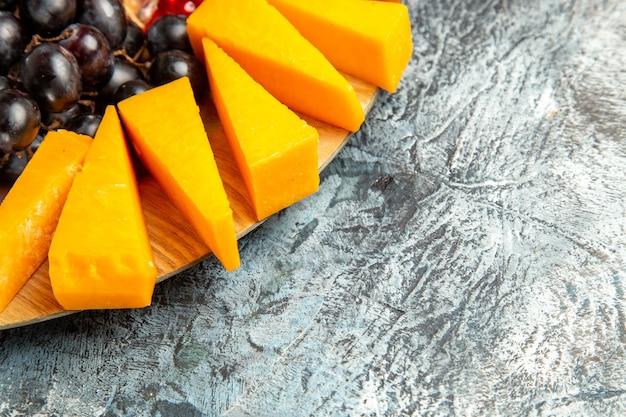 暗い背景のコピースペースの楕円形のサービングボード上の底面図チーズピースブドウ