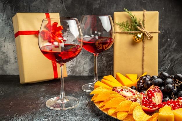 Вид снизу кусочки сыра, мясо, виноград и гранат на овальной сервировочной доске, бокал вина, рождественские подарки на темном фоне