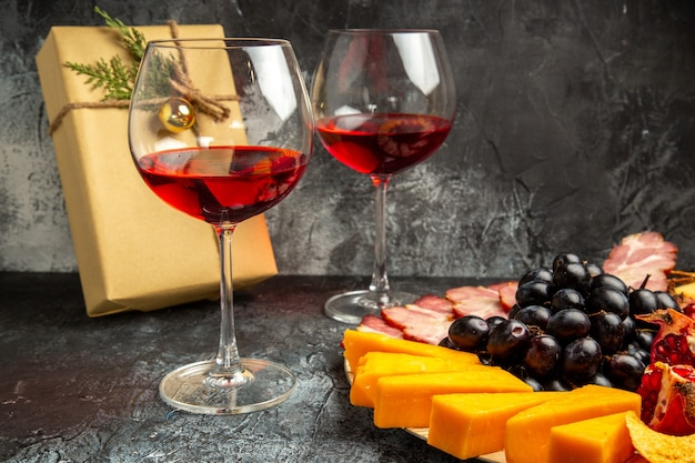 Bottom view cheese pieces meat grapes and pomegranate on oval serving board glass of wine xmas gift on dark