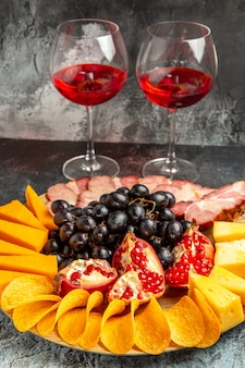 Bottom view cheese pieces meat grapes and pomegranate on oval serving board wine glasses on dark background