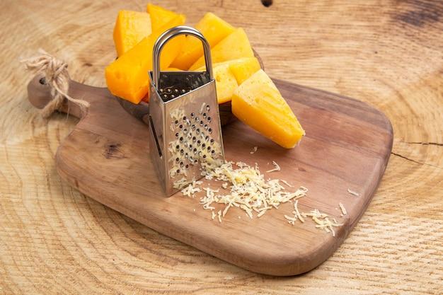 Fette di formaggio vista dal basso nella grattugia della ciotola sul tagliere su superficie di legno