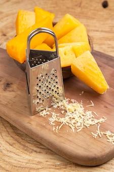 Fette di formaggio vista dal basso in una grattugia di legno della scatola della ciotola sul tagliere su una superficie di legno
