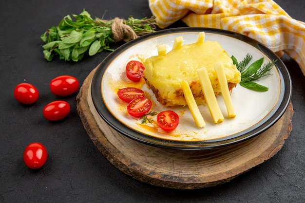 Vista dal basso pane di formaggio pomodorini e patate su piatto su tavola di legno su sfondo nero