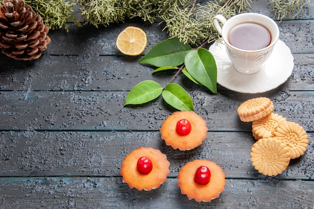 Bottom view cherry cupcakes cone fir-tree branches slice of lemon a cup of tea biscuits on dark wooden background