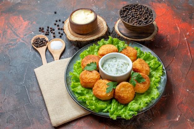 Вид снизу куриные наггетсы, салат на тарелке, черный перец в деревянной миске, деревянные ложки на темном столе