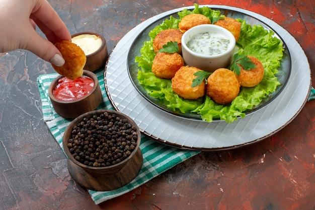 Vista dal basso pepite di pollo lattuga e salsa sul piatto pepe nero in ciotola salse in piccole ciotole pepita in mano femminile sul tavolo scuro