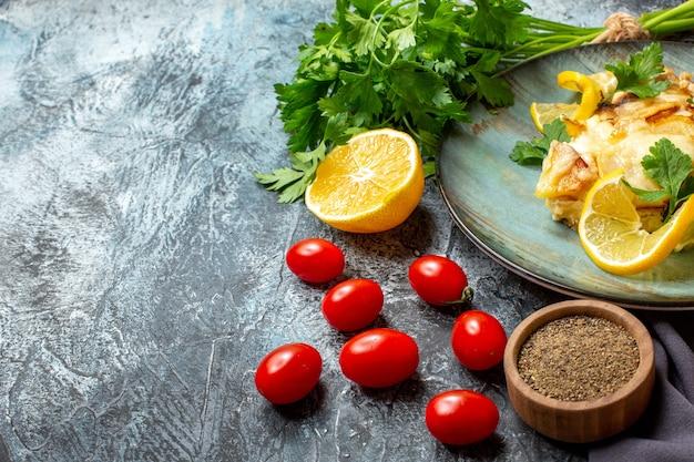 Vista dal basso pollo con formaggio su piatto mazzo di pomodorini limone prezzemolo su sfondo grigio con copia posto