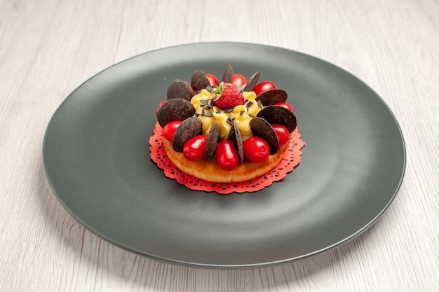 Torta al cioccolato vista dal basso arrotondata con corniolo e lampone al centro nel piatto grigio su fondo di legno bianco