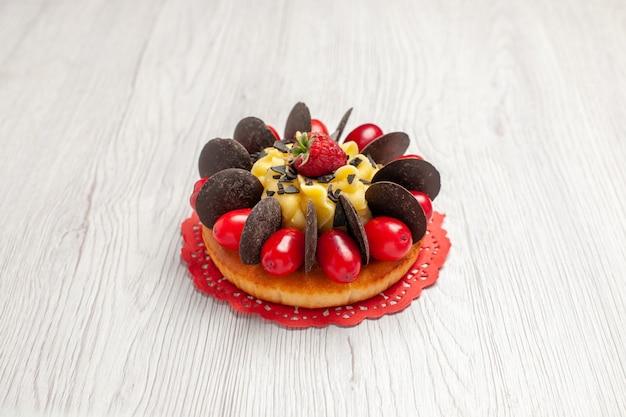 白い木製の背景に赤い楕円形のレースのドイリーにベリーとチョコレートケーキの底面図