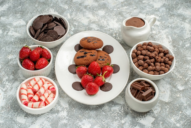 Bottom view chocolate cookies strawberries and round chocolates on the white oval plate and bowls with candies strawberries chocolates cereals and cacao on the grey-white background