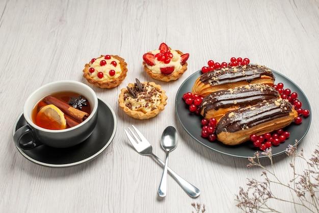 흰색 나무 테이블에 대각선 벡터에 회색 접시 쿠키 레몬 계피 차 숟가락과 포크에 하단보기 초콜릿 eclairs 및 건포도