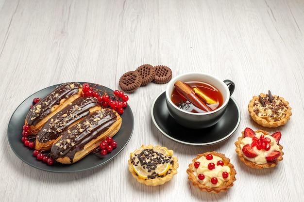 Vista dal basso bignè al cioccolato e ribes sui biscotti crostate della banda grigia e tè alla cannella al limone sul tavolo di legno bianco