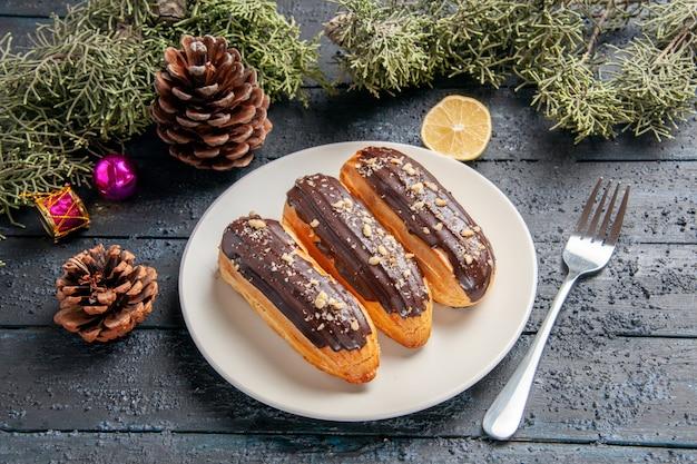 Вид снизу шоколадные эклеры на белой овальной тарелке, шишки, еловые листья, елочные игрушки, ломтик лимона и вилка на темном деревянном столе