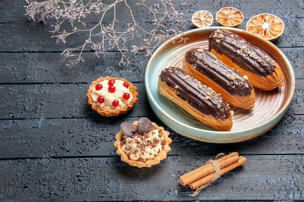 Bottom view chocolate eclairs on oval plate dried flower branch tarts cinnamon and dried oranges on the dark wooden table with copy space