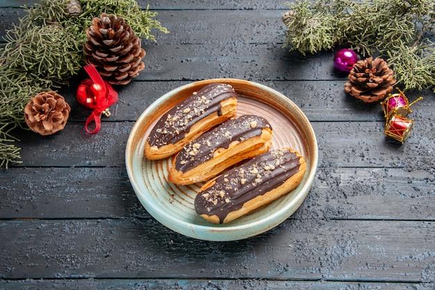 Vista dal basso eclairs al cioccolato su un piatto ovale pigne di natale giocattoli foglie di abete su fondo di legno scuro