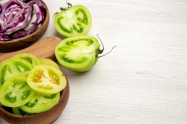 밑면 다진 녹색 토마토는 여유 공간이있는 흰색 표면에 그릇에 붉은 양배추를 자릅니다.