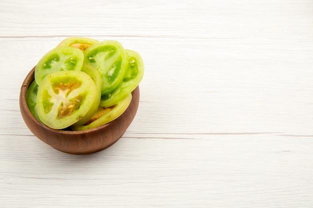 여유 공간이있는 흰색 테이블에 나무 그릇에 밑면 다진 녹색 토마토