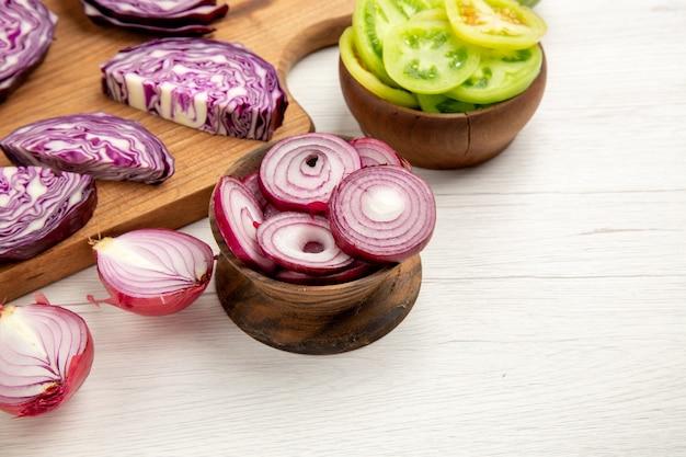 하단보기 그릇에 다진 양파는 나무 보드에 붉은 양배추를 잘라 흰색 표면에 그릇에 빨간 토마토를 잘라