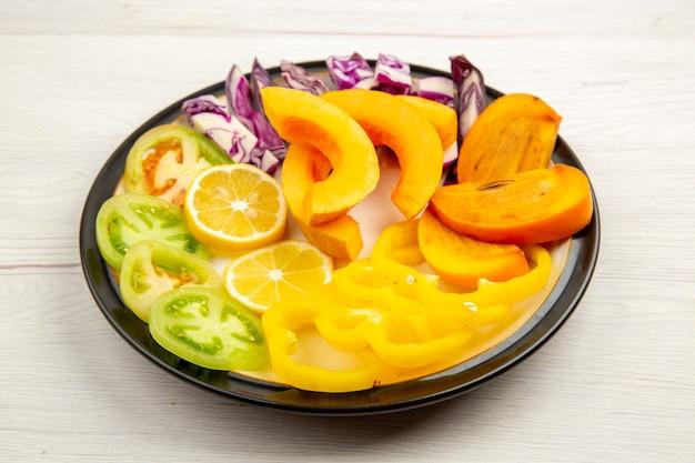 하단보기 다진 야채와 과일 호박 피망 감 붉은 양배추 녹색 토마토 흰색 표면에 검은 접시에
