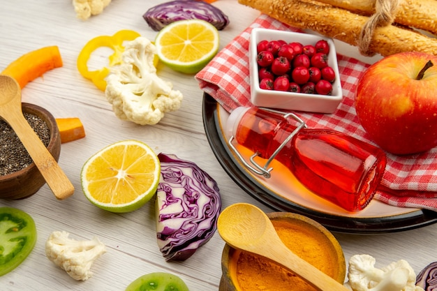 Vista dal basso verdure tritate pane rosso bottiglia di pane sul tovagliolo su piatto rotondo varie spezie in piccole ciotole sul tavolo