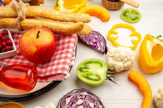 底面図白いテーブルの上の丸いプレート上のナプキンに刻んだ野菜リンゴパン赤いボトル