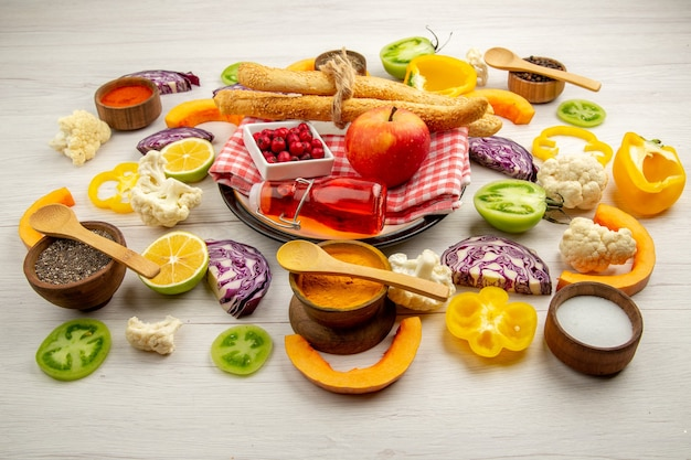 底面図みじん切り野菜リンゴパン赤いボトルナプキンの白い大皿テーブルの上の小さなボウルにさまざまなスパイス