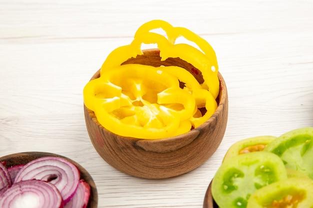 흰색 표면에 나무 그릇에 밑면 다진 야채 피망 녹색 토마토 붉은 양배추