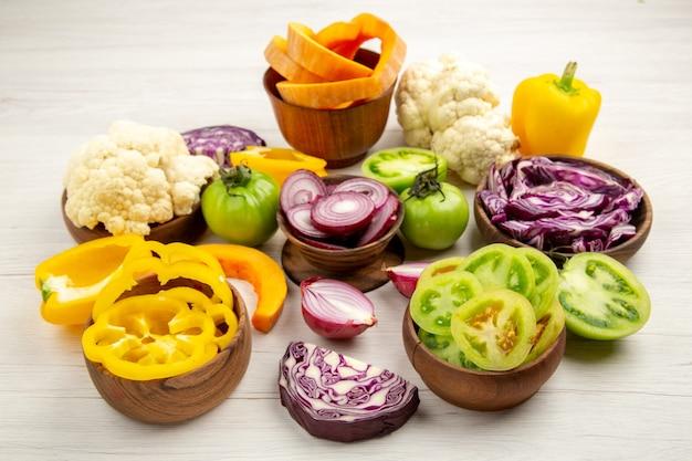Vista dal basso verdure tritate peperoni pomodori verdi cavoli rossi cipolle cavolfiori zucche in ciotole su tavolo di legno bianco
