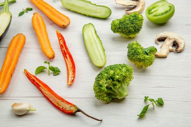Vista dal basso verdure tritate cetriolo funghi broccoli carota peperoncino sul tavolo di legno grigio