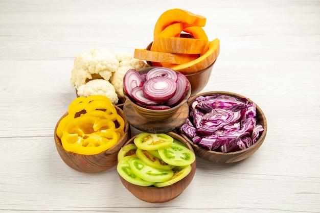 Vista dal basso verdure tritate tagliare cavolo rosso tagliare zucca tagliare peperoni gialli tagliare cipolla tagliare pomodori verdi cavolfiore in ciotole su superficie di legno