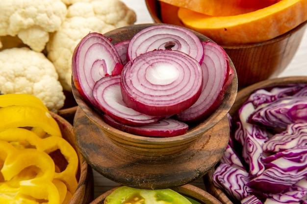 Vista dal basso verdure tritate tagliare cavolo rosso tagliare zucca tagliare peperoni gialli tagliare cipolla tagliare pomodori verdi cavolfiore in ciotole