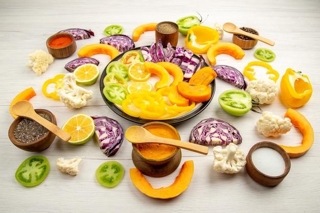 Vista dal basso frutta e verdura tritate zucca cachi cavolo rosso limone pomodori verdi cavolfiore peperoni gialli su piatto rotondo spezie in piccole ciotole sul tavolo bianco