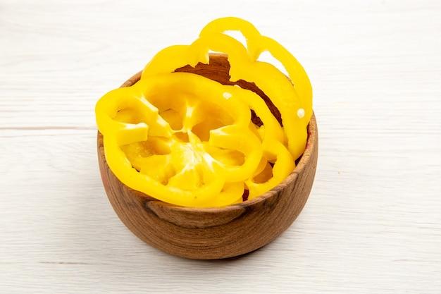 Peperoni dolci gialli tagliati vista dal basso in ciotola di legno sul tavolo bianco