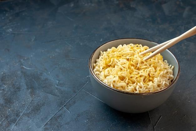 Vista dal basso bacchette di ramen asiatico noodles in una ciotola bianca sul tavolo scuro waribashi