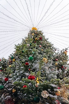 Bottom view of christmas tree decoration with toys and garlands. city festive decor during winter holidays.