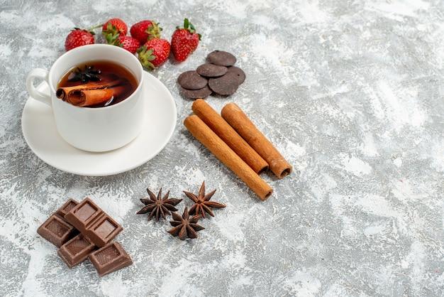 Vista dal basso tè alla cannella ai semi di anice e alcune fragole cioccolatini cannellini semi di anice sul lato sinistro del tavolo