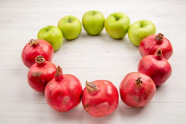 Vista dal basso di fila di melograni e mele frutta fresca sul tavolo grigio