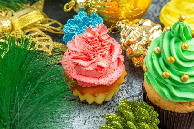 Bottom view colorful cupcakes xmas ornaments on grey background