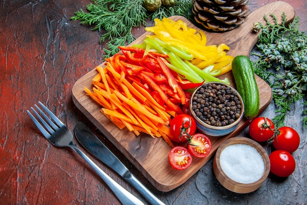 Vista dal basso peperoni tagliati colorati pepe nero pomodori cetriolo sul tagliere rami di pino sale forchetta e coltello sul tavolo rosso scuro