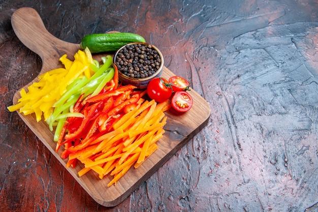 底面図カラフルなカットペッパー黒コショウトマトきゅうりのチョッピングボード上のコピースペースのある濃い赤のテーブル