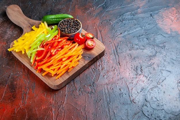 底面図カラフルなカットペッパー黒コショウトマトきゅうりまな板のコピースペースと濃い赤のテーブル