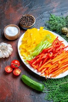 Vista dal basso peperoni tagliati colorati su piatto sale e pepe nero pomodori aglio cetriolo sul tavolo rosso scuro