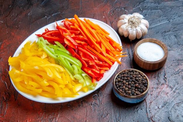 Vista dal basso peperoni colorati tagliati su piatto bianco pepe nero sale aglio su tavolo rosso scuro