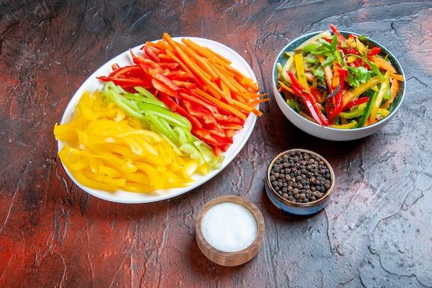Vista dal basso peperoni tagliati colorati su piatto bianco insalata di verdure in una ciotola pepe nero sale aglio su tavolo rosso scuro
