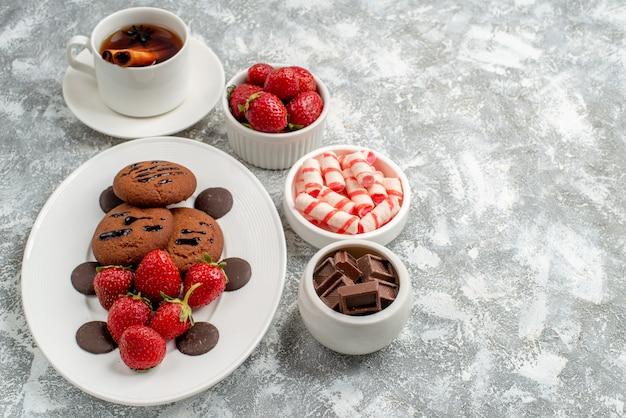 Vista dal basso biscotti fragole e cioccolatini rotondi sul piatto ovale ciotole di caramelle fragole cioccolatini cannella tè all'anice sul lato sinistro del tavolo grigio-bianco