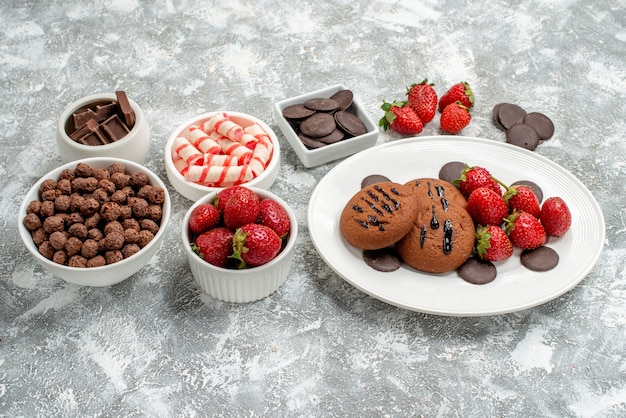 Bottom view cookies strawberries and round chocolates on the oval plate bowls with candies strawberries chocolates cereals on the grey-white table