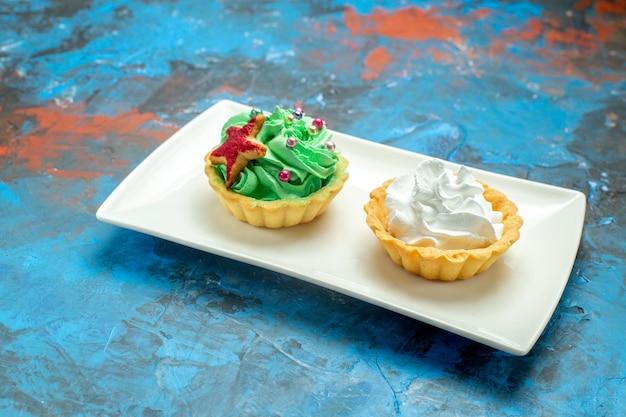 Вид снизу кремовые пирожные на белой прямоугольной тарелке на сине-красной поверхности