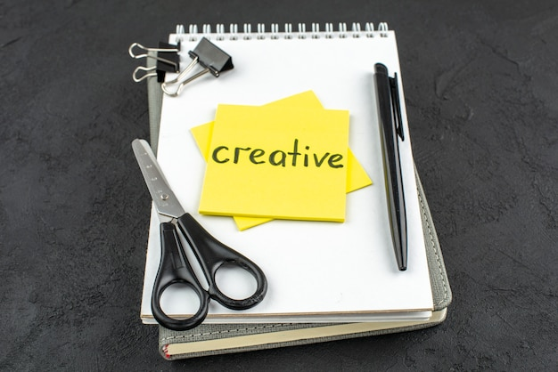Bottom view creative written on yellow sticky note scissors black pen binder clips on notebook on dark background