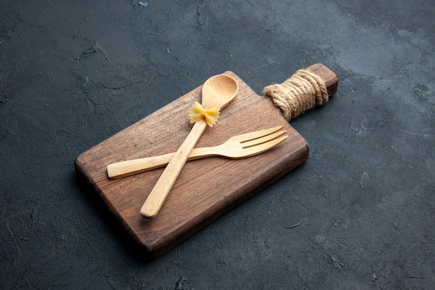 Bottom view crossed wooden spoon and fork on wooden serving board on dark surface with copy place
